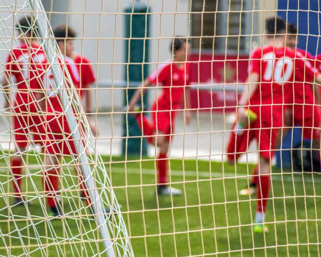 football players stretching shown through football goal netting